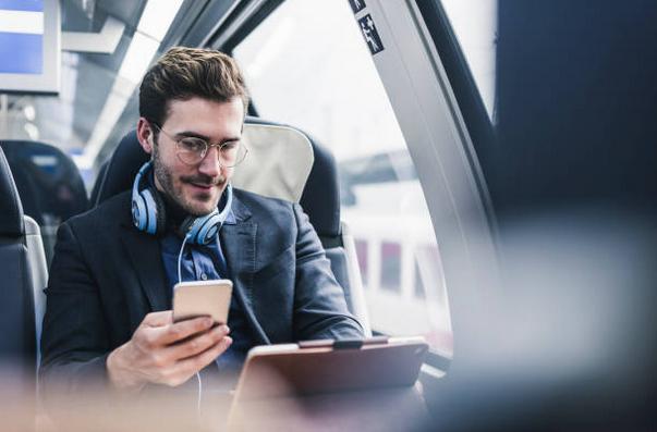 Homme dans un transport en commun avec une tablette et un téléphone portable